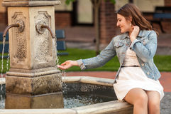 Beautiful woman holding hand under fountain Royalty Free Stock Photo