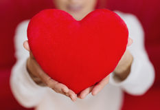 Beautiful woman holding heart in hand - care and love Royalty Free Stock Photography