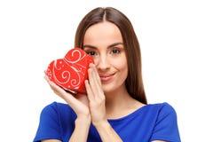Beautiful woman holding heart shaped gift Stock Photo