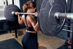 Beautiful Woman Holding Heavy Barbell. Back of beautiful strong woman lifting heavy barbell performing shoulder press during crossfit workout in modern gym Stock Photos