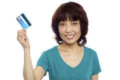 Beautiful woman holding her credit card out Stock Photo