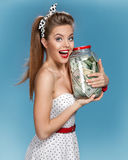 Beautiful woman holding her retirement account of american dollars in a transparent bottle (jar)  and happy smiling. Shopping con Stock Image