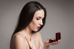 Beautiful woman holding jewelry box. Surprised beautiful woman holding jewelry box with an engagement ring in it. Happy young woman after marriage proposal Royalty Free Stock Images