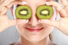 Beautiful woman holding kiwi fruits in front of her eyes Stock Photos