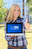 Beautiful woman holding laptop with login panel on screen and th Royalty Free Stock Photography