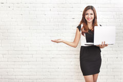 Beautiful woman holding a laptop while presenting a copy space. Portrait of beautiful woman holding a laptop while presenting a copy space on white brick wall royalty free stock photos