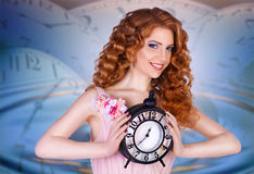 Beautiful woman holding a large clock. Beauty portrait of cheerful red-haired girl with long curly hair. against the background of hours Royalty Free Stock Photography