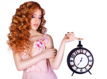 Beautiful woman holding a large clock. Beauty portrait of cheerful red-haired girl with long curly hair  isolated on a white background Royalty Free Stock Photos