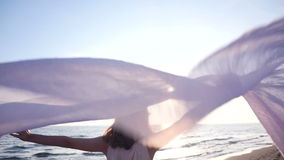 Beautiful woman holding light fabric on the beach and enjoy the sunset