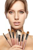Beautiful woman holding makeup brushes set Stock Image