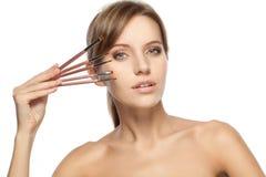 Beautiful woman holding makeup brushes set Royalty Free Stock Photos