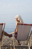 Beautiful Woman Holding Man's Hand While Sitting On Deckchair. Portrait of beautiful woman holding man's hand while sitting on deckchair at beach Royalty Free Stock Image