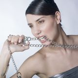 Beautiful woman holding metallic chain. A beautiful woman holding up metallic chain and biting it Royalty Free Stock Images