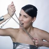 Beautiful woman holding metallic chain. A beautiful woman holding up metallic chain and biting it Stock Images
