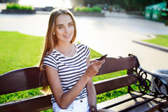 Beautiful woman holding mobile phone in hand and sitting on the bench Stock Photo