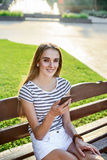 Beautiful woman holding mobile phone in hand and sitting on the bench Stock Photography