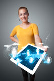 Beautiful woman holding modern tablet with social icons Royalty Free Stock Photography