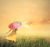 Beautiful woman holding multicolored umbrella in green grass fie Royalty Free Stock Photos