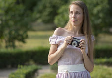 Beautiful woman is holding old fashioned camera in hand, outdoors. Stock Image