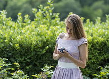 Beautiful woman is holding old fashioned camera in hand, outdoors. Stock Images
