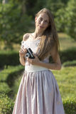 Beautiful woman is holding old fashioned camera in hand, outdoors. Stock Photos