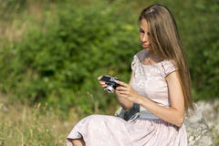 Beautiful woman is holding old fashioned camera in hand, outdoors. Stock Photography