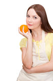 Beautiful woman holding an orange fruit. In her hand Royalty Free Stock Image