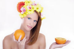 Beautiful woman holding oranges. Beauty portrait - young woman with flowers in hair holding oranges Stock Photo