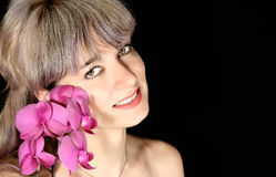 Beautiful woman holding an orchid near the face. On black background Stock Photo
