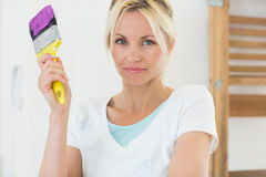 Beautiful woman holding paint brush in new house Royalty Free Stock Photos