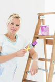 Beautiful woman holding paint brush in new house Royalty Free Stock Images