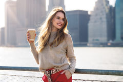 Beautiful woman holding paper coffee cup and enjoying the walk in the city Stock Images