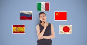 Beautiful woman holding pen and thinking while standing by flags against blue background Stock Photo