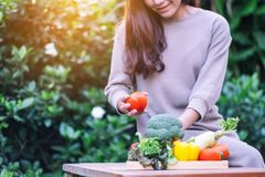 A beautiful woman holding and picking a fresh mixed vegetables from a wooden tray