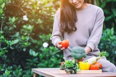 A woman holding and picking a fresh mixed vegetables from a wooden tray on the table