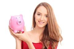 Beautiful woman holding a piggybank Stock Photos