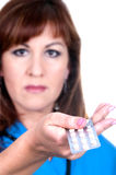 A beautiful woman holding a pill, focus on pill Royalty Free Stock Image