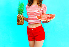 Beautiful woman is holding a pineapple and a slice of watermelon. Over a colorful blue background Royalty Free Stock Photo