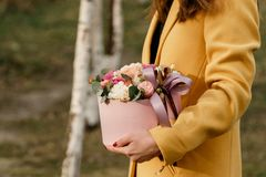 Beautiful woman holding pink box with flowers. Gift to Women`s Day. Agency floral design, place text royalty free stock photography