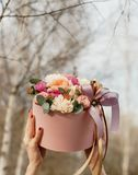 Beautiful woman holding pink box with flowers. Gift to Women`s Day. Agency floral design, place text stock images
