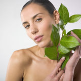 Beautiful woman holding plant. Portrait of a beautiful naked and relaxed woman holding a plant . Beauty and wellness concept Royalty Free Stock Photo