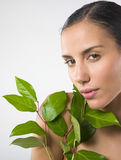 Beautiful woman holding plant. Portrait of a beautiful naked and relaxed woman holding a plant . Beauty and wellness concept Royalty Free Stock Photos