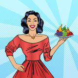 Beautiful Woman Holding a Plate with Fruits. Pop Art Housewife Royalty Free Stock Photography