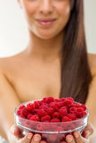Beautiful woman holding a pot of raspberries Royalty Free Stock Image