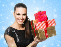 Beautiful woman holding presents over a snowy backgrounde background Stock Image