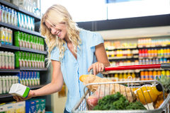 Beautiful woman holding product. In supermarket stock photography