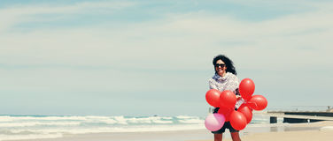 Beautiful woman holding red balloons Stock Photography
