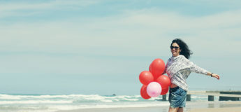 Beautiful woman holding red balloons Stock Images