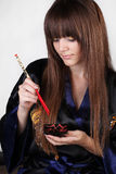 Beautiful woman holding red chopsticks. Isolated on grey background Royalty Free Stock Image