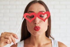 Beautiful woman holding red glasses-mask in the shape of heart a. Smiling brunette holding red glasses-mask in the shape of heart and kissing something, white Royalty Free Stock Photography